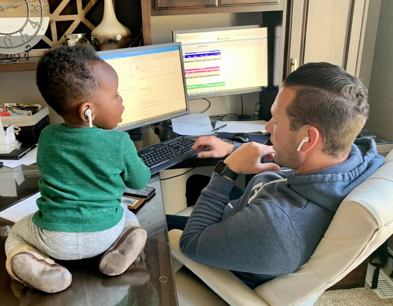HTLF Employee with child at home working on a computer